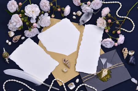 Decorated envelopes with empty paper sheets, quill, decorations and roses. Mystic and romantic background with copy space and blank, vintage romantic concept for mock up, top view