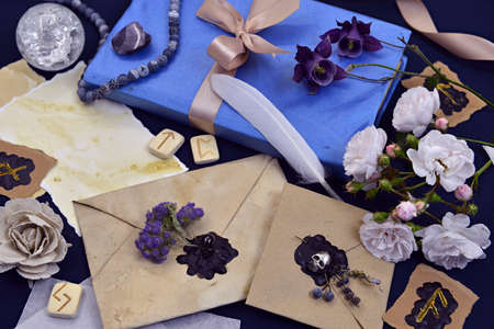 Decorated envelopes, old book, runes and flowers on witch table. Mystic and romantic background with copy space and blank, vintage romantic concept for mock up, top view 版權商用圖片