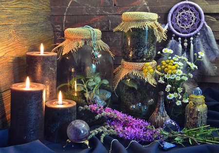 Still life with black candles, bottles and jars with plants and herbs on witch table.  Esoteric, gothic and occult background, Halloween mystic concept.