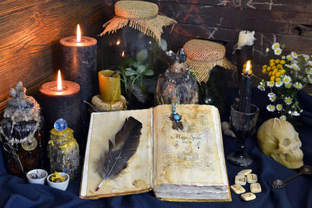 Still life with spell book, magic jars with plants and potion on witch table. Esoteric, gothic and occult background, Halloween mystic concept.