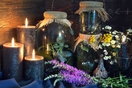 Black candles and magic bottles with plants and herbs on witch table.  Esoteric, gothic and occult background, Halloween mystic concept.