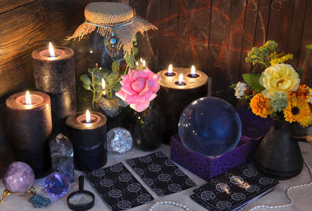 Mysterious still life with tarot cards, black candles and crystal ball on witch table. Esoteric, gothic and occult background with magic objects. Halloween fortune telling concept. Zdjęcie Seryjne