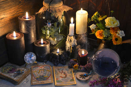 Mysterious still life with old tarot cards, crystal ball and black candles on witch table. Esoteric, gothic and occult background with magic objects. Halloween fortune telling concept