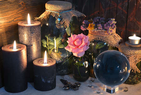 Mysterious still life with blak candles, crystal ball and rose on witch table. Esoteric, gothic and occult background with magic objects. Halloween fortune telling concept.