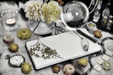 Styled still life with open book diary with copy space, crystal ball, runes, yellow flowers and ritual magic object on witch table. Esoteric, gothic and occult background, Halloween mystic concept.