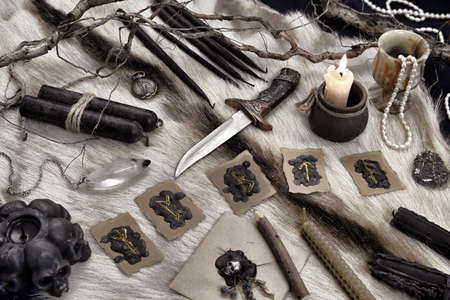 Still life with runes, ritual knife and black candles on witch table. Esoteric, gothic and occult background, Halloween mystic concept.
