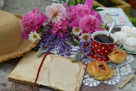 Still life with open diary book, bunch of flowers, cup and hat on the table.  Vintage botanical background with plants, home hobby still life with gardening objects and nature. Zdjęcie Seryjne