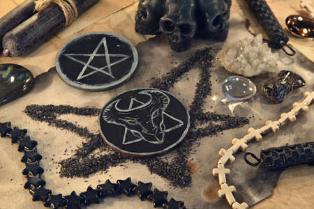 Scary symbols of devil and pentagram with black candles and crystals on old paper. Esoteric, gothic and occult background, Halloween mystic concept. Banque d'images