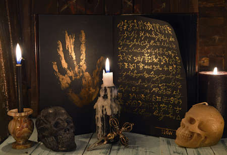 Sell soul to the devil concept with open book full of golden mystic symbols, skull and candles. Esoteric, gothic and occult background, Halloween mystic concept. Banque d'images