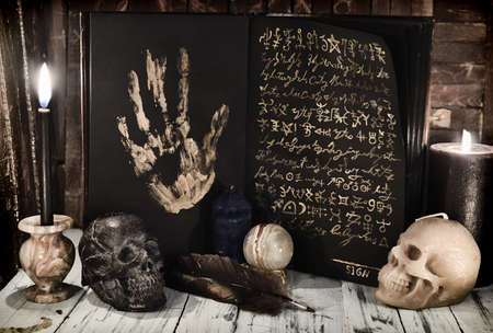 Evil book wih black pages and mystic symbols, burning candles and skull on wooden table. Sell soul to the devil concept. Esoteric, gothic and occult background, Halloween mystic concept.