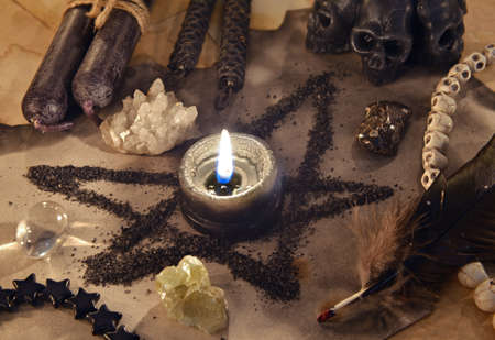 Pentagram symbol made of black salt with  candle on old paper. 免版税图像
