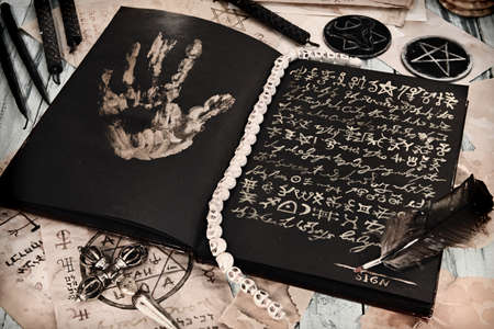 Still life with grimoire book of magic spell, black candles on witch table, sell soul to the devil concept. Esoteric, gothic and occult background, No foreign language, all signs are fantasy.