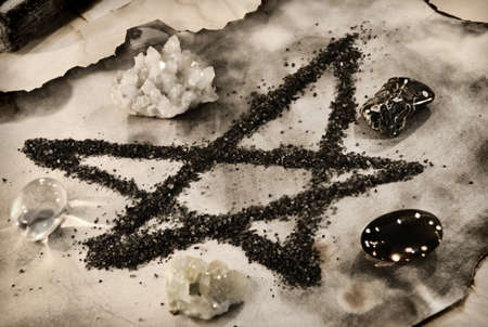 Pentagram symbol made of black salt with crystals on paper. Esoteric, gothic and occult background, Halloween mystic concept.