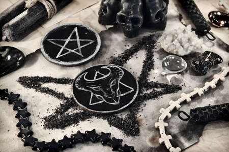 Scary symbols of devil and pentagram with scull candle and ritual objects on wooden table. Esoteric, gothic and occult background, Halloween mystic concept.
