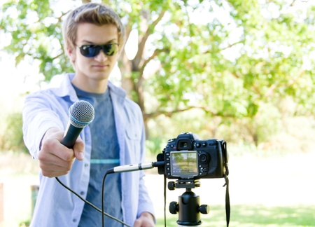 Young man holding a microphone connected to a D SLR. Focus on the microphone only.