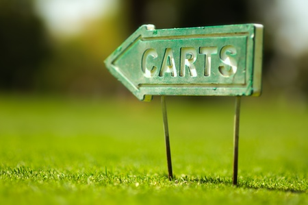 Golf carts sign on a golf field. Small depth of field.