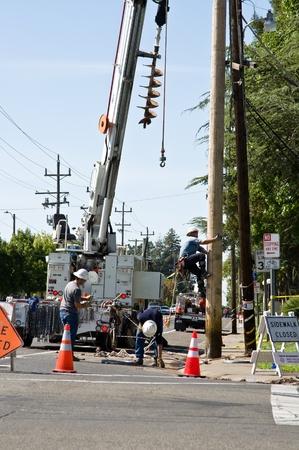 municipal: SACRAMENTO - AUGUST 29: Unidentified Sacramento Municipal Utility District  (SMUD) technicians clean up around a power pole and fix it after car accident on College Oak Avenue, at the American River College parking entrance, on August 29, 2011.