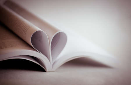 colorize: close up of an open book with heart shaped pages, colorize in pink, vignetting
