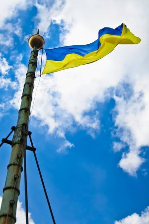 Flag of Ukraine with flag pole waving in the wind on front of blue sky with clouds