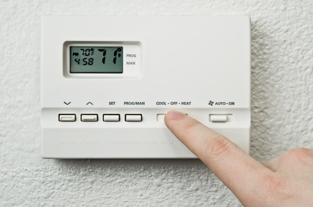 digital thermostat and finger pressing button photo