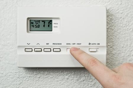 digitale thermostaat en vinger die op de knop