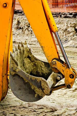 Yellow backhoe claw bucket on heavy duty construction machine photo