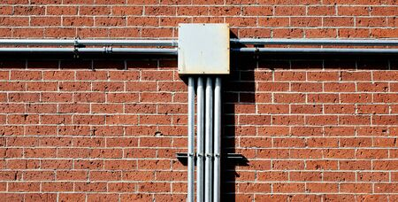 junctions: electrical junction box on red brick wall Stock Photo