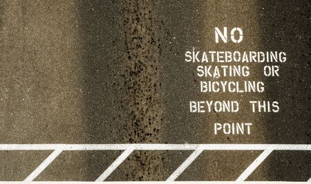 No skateboarding skating or bicycles beyond this point, sign painted on footpath Stock Photo - 13295891