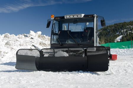 groomer: A snow groomer machine in mountains