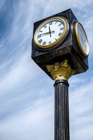 a vintege street clock on a poll