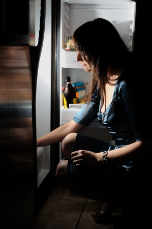 young woman in a dress loking insede of fridge photo