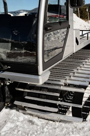 groomer: A gray silver snow groomer machine in mountains