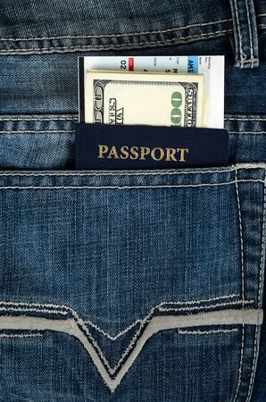 passport with boarding pass and money in blue jeans photo