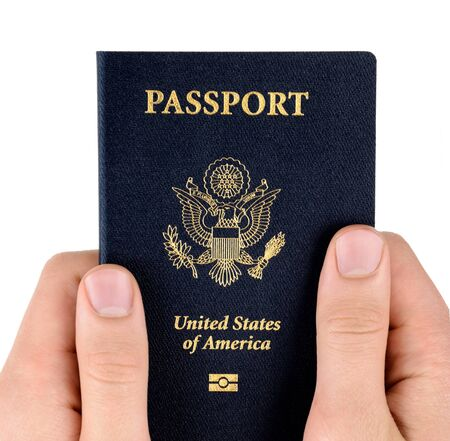 citizenship: person hands hold US passports on a white background