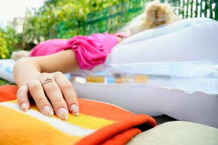 Jong meisje liggend op matras, focus op de hand Stockfoto