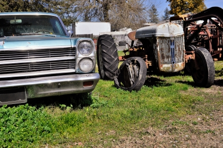 junk yard: Old rusted car and tractor  in junk yard