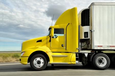 Große gelbe LKW auf der Autobahn mit bewölktem Himmel Standard-Bild - 23286541