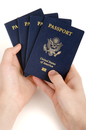 two hands holding US passports on a white background