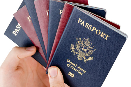 man holds bunch of passports, USA passport on the front