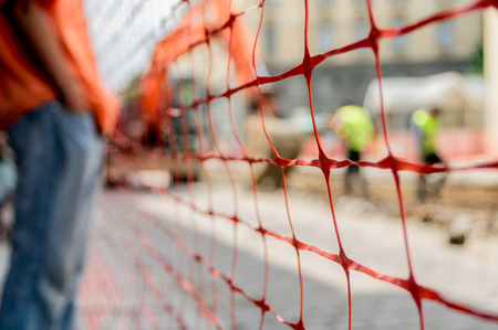 on site: orange construction site net around construction site, shallow depth of field Stock Photo