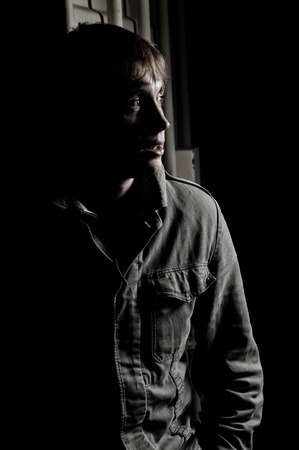 criminal investigation: Portrait of a young man waiting in shadow