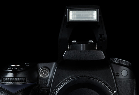 eos: Professional modern DSLR camera with open flash, low key image