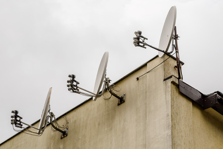 antenna: Three Satellite dishes on the roof of a house, overcast sky Stock Photo