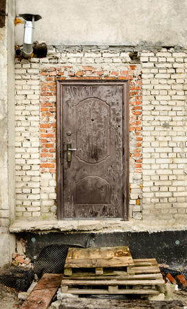 Old door in rustic brick wall with pallets as steps, constriction site Standard-Bild - 100130054