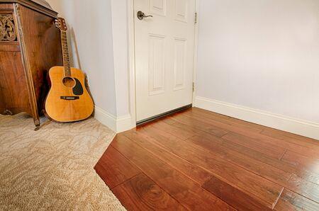 An acoustic guitar on carpet, wooden floor. Room