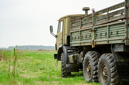 Side of a Military Truck with its bed on green field