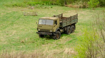 Military truck placed on green field grass background. Stock fotó