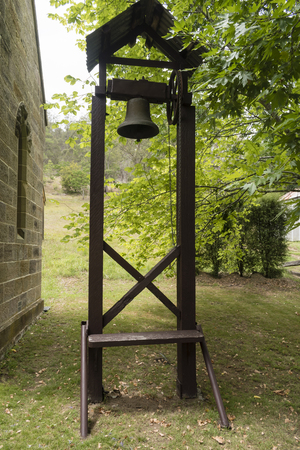old rustic bell with sandstone building and greenery Фото со стока - 100346290