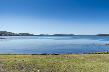 Vivid blue Calm and Clear lake with greenery and hills Фото со стока