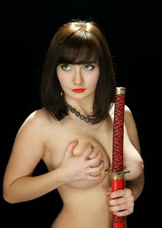 bare breasts: The bared girl with the Japanese sword Stock Photo
